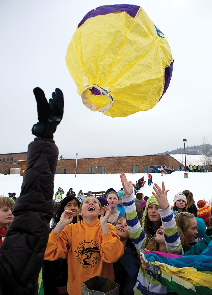 Steamboat Springs Middle School sixth-grader Tehya Johnson, middle, reacts as a balloon takes flight from the Steamboat Springs Middle School football field Monday morning.
