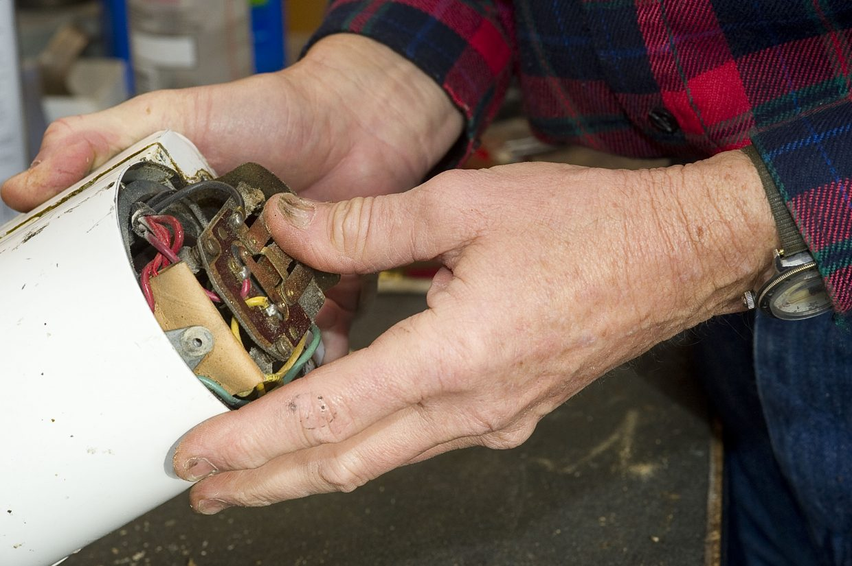Bill Fetcher examines the workings of a 1985 KitchenAid mixer while repairing a gear.