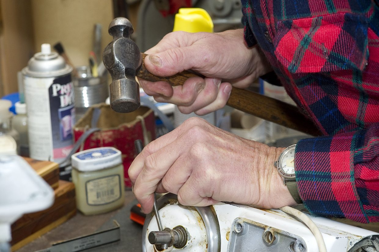 Bill Fetcher removes a pin from the drive on a 1985 KitchenAid mixer while repairing a gear.