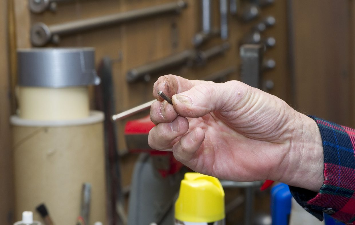 Bill Fetcher examines a pin he removed from a 1985 KitchenAid mixer while repairing a gear.