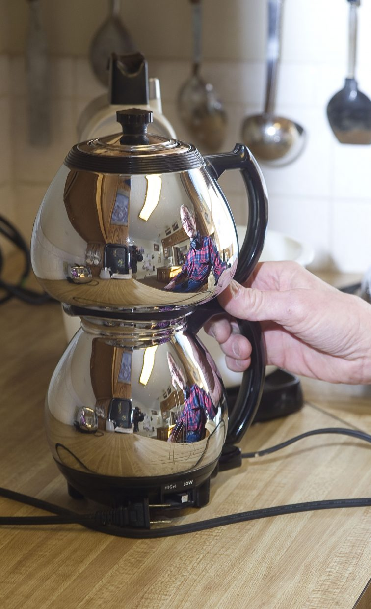 Longtime Steamboat Springs resident Bill Fetcher is reflected in a Sunbeam vacuum coffee maker that he restored and still uses in his kitchen. He also repairs clocks, watches and musical instruments.