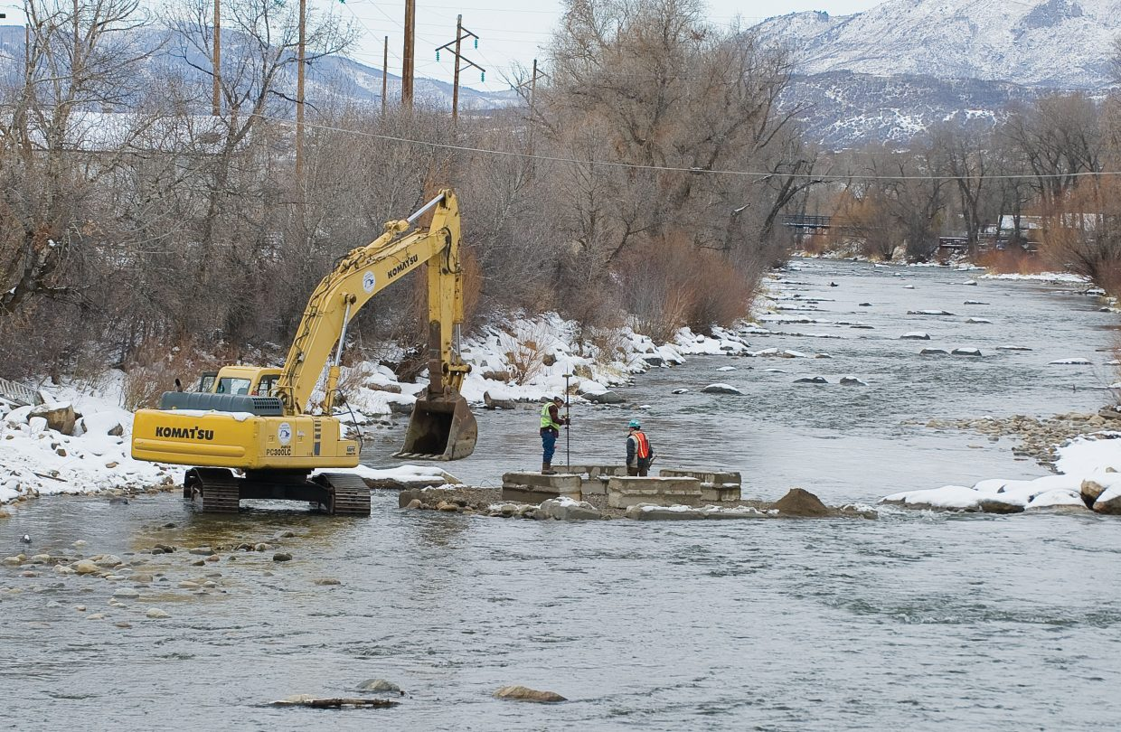Construction crews work to construct a pillar for a temporary bridge in the middle of the Yampa River on Monday afternoon. Crews will use the temporary bridge to place a permanent pedestrian bridge over the Yampa near 13th Street sometime next week.