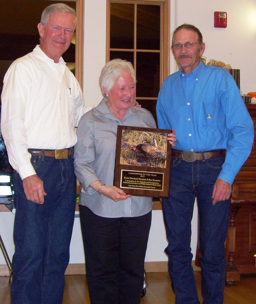 Ron Normann, from left, and Karin Utterback-Norman accept the 2011 Landowner of the Year award from Larry Monger, chairman of the Upper Yampa Habitat Partnership Program committee. They were honored Oct. 29 at the annual Agriculture Fall Gathering.