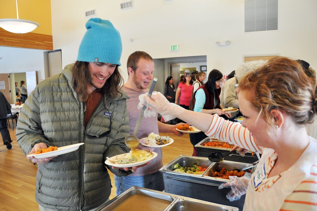 Gaby Strnad, right, pours some gravy on Kyle Telker's plate during the Routt County United Way Community Thanksgiving Dinner.