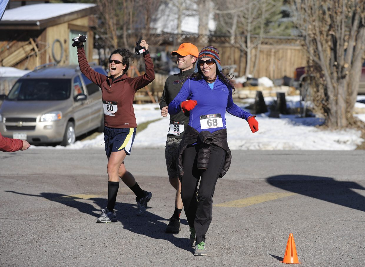 Steamboat Springs Winter Running Series Turkey Trot participants, from left, Kelsey McMillan, Gavin McMillan and Morgan Rogers come across the finish line Thursday during the annual Thanksgiving day race.