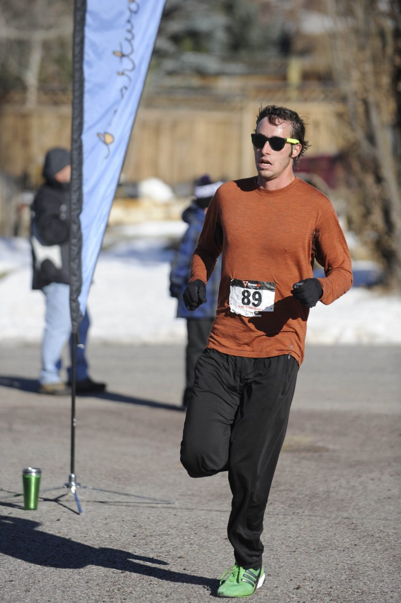 Gabriel Small crosses the finish line first during Thursday's Steamboat Springs Winter Running Series Turkey Trot.
