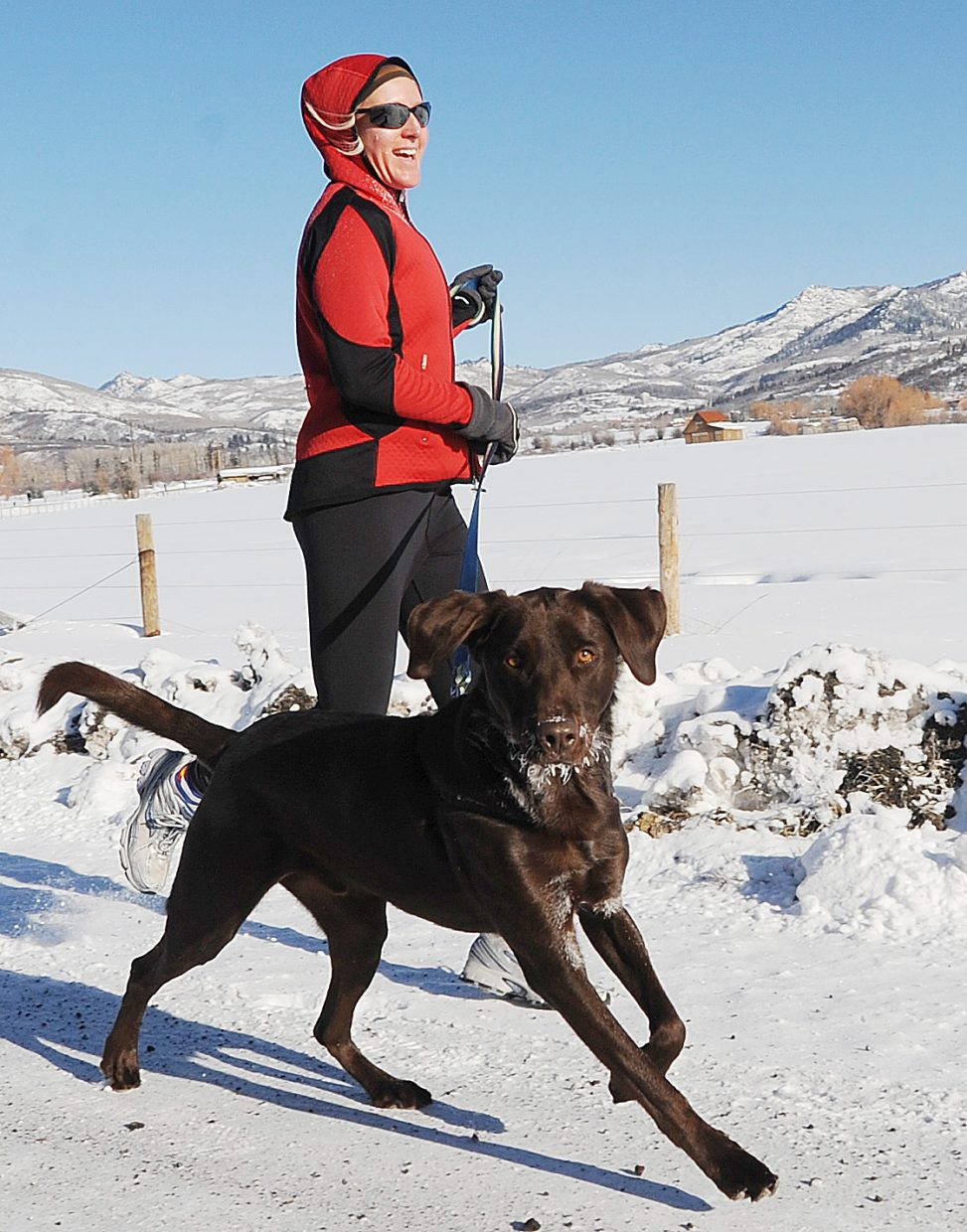 Beth Egelhoff and her dog, Oreo, run in Thursday's Turkey Trot race in Steamboat Springs.