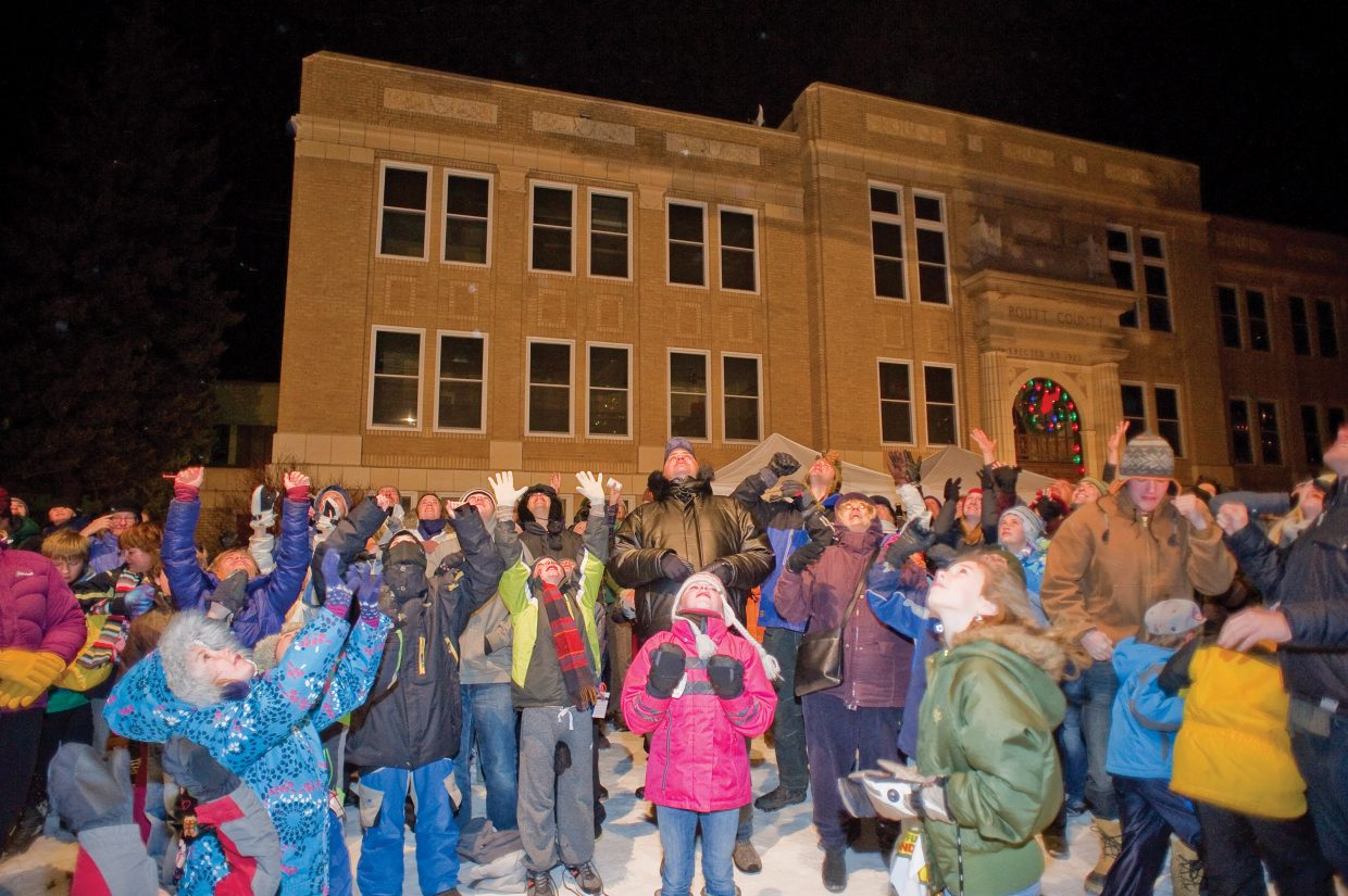 A large crowd waits for a fireman to drop ping pong balls from the ladder of a fire truck Friday night during the seventh annual Light Up the Night community tree lighting ceremony, which was held on the lawn of the Routt County Courthouse. Each ping pong ball had a deal from a downtown business written on it.