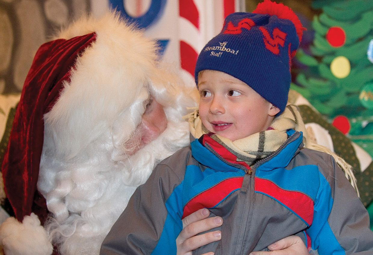 Hayden Noyes, who will turn 5 on Christmas, listens to Santa Claus on Friday night during the seventh annual Light Up the Night community tree lighting ceremony, which was held on the lawn of the Routt County Courthouse.