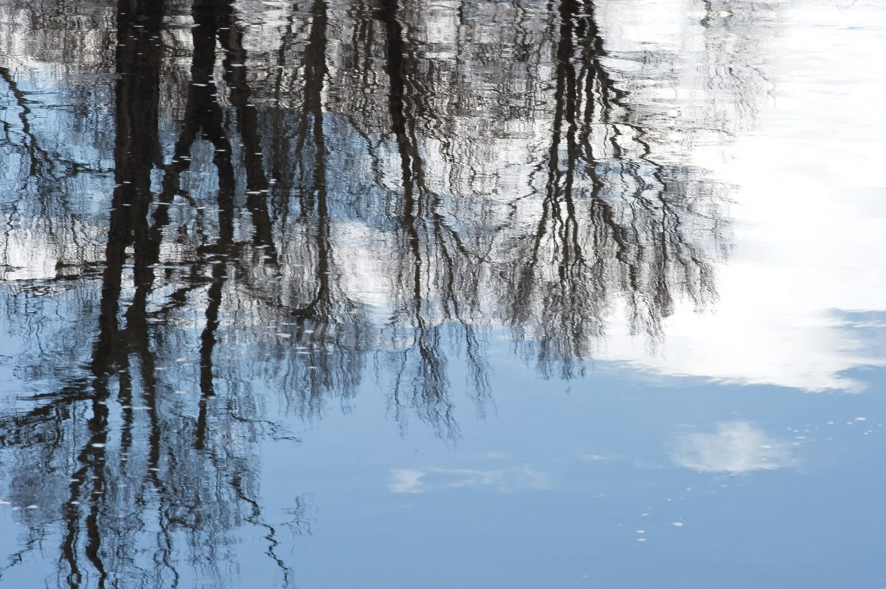 Trees are reflected in the waters of the Yampa River west of Steamboat Springs on Friday afternoon. Steamboat saw some light snow Friday evening, but mild, sunny weather is expected to dominate the forecast for the next few days.