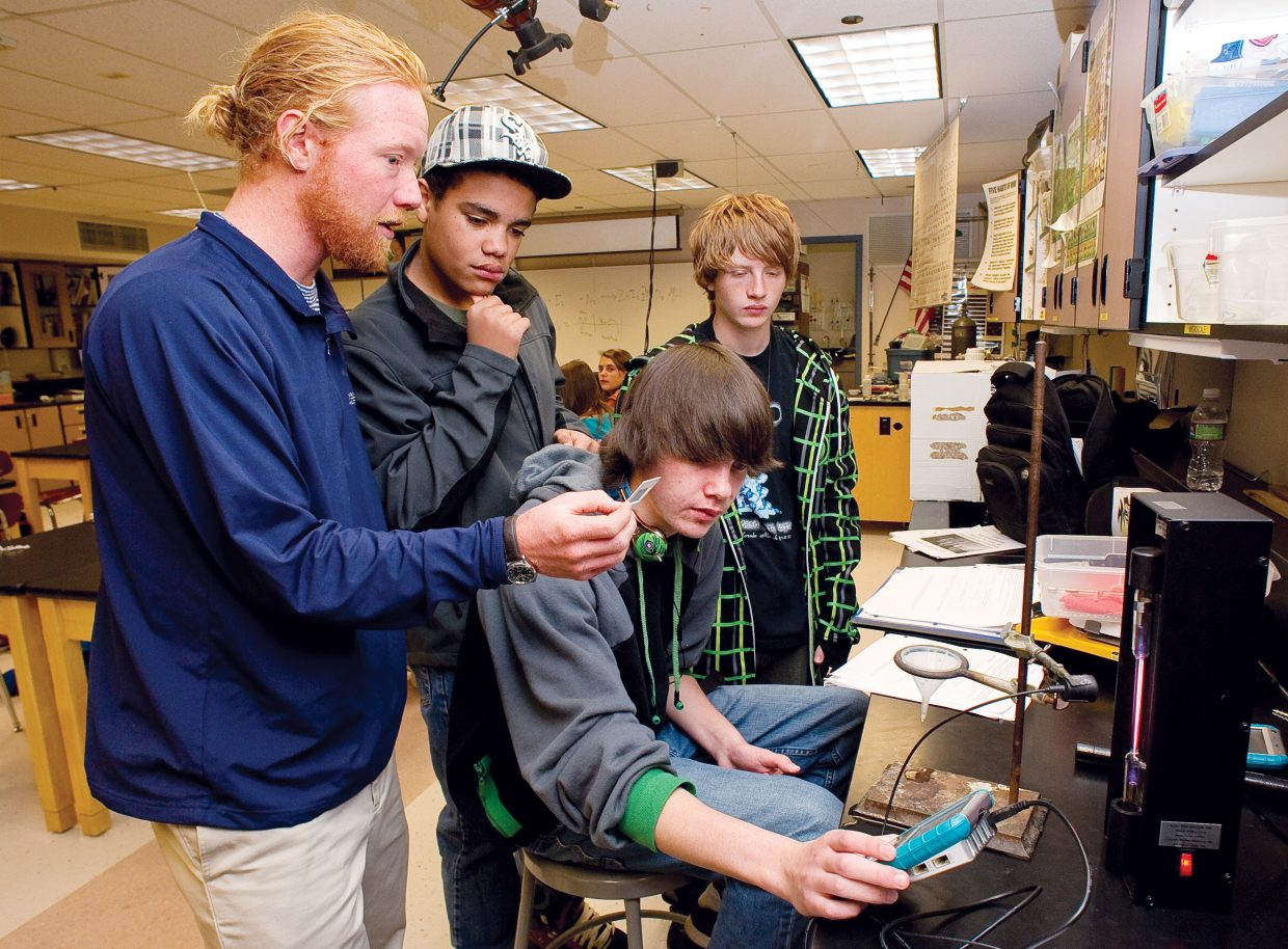 Substitute teacher Rodney Beall talks with students, from left, Harry Jenkins, Ryan Graves and Preston Anderson during a science class Tuesday at Steamboat Springs High School. The Steamboat Springs School District was accredited with distinction for the second year in a row by the state of Colorado.