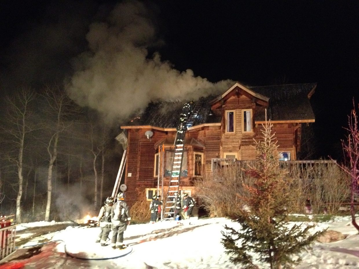 Steamboat Springs Fire Rescue firefighters finish knocking down a chimney and roof fire in Strawberry Park on Monday night.