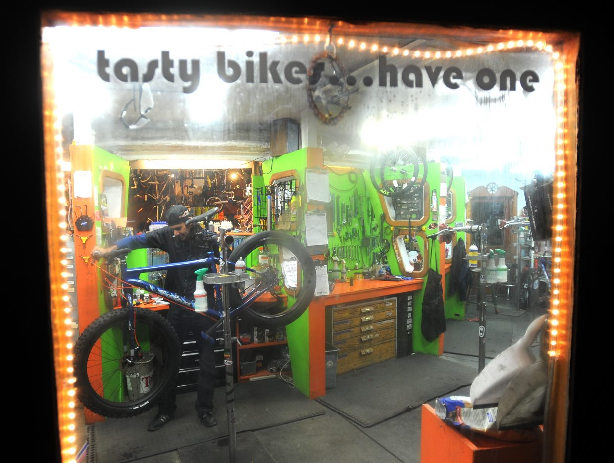 Essam Welch tunes a bike on a dark afternoon in 2012 at Orange Peel Bicycle Service in Steamboat Springs.