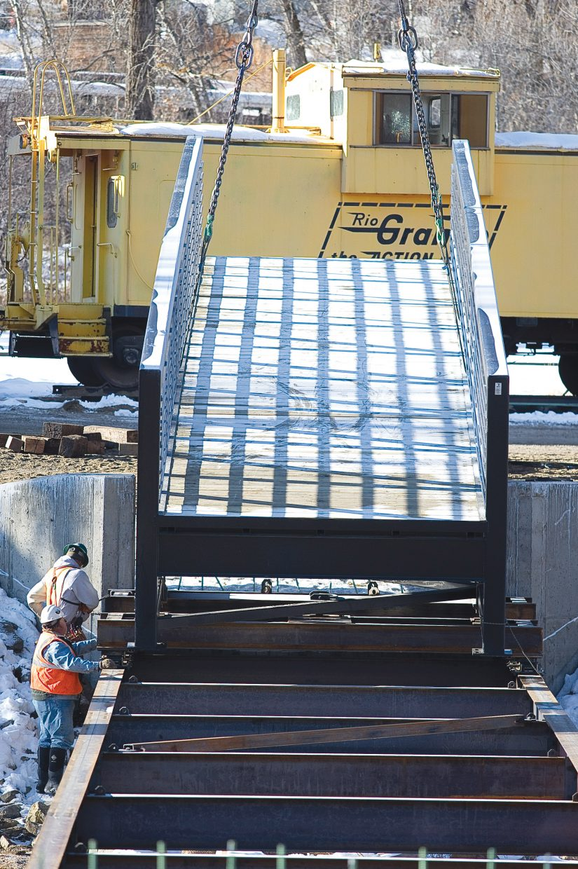Crews secure a pedestrian footbridge to a rail system Wednesday before pulling it across the Yampa River near 13th Street. The bridge will connect the Yampa River Core Trail in front of the Depot Art Center to West Lincoln Park.