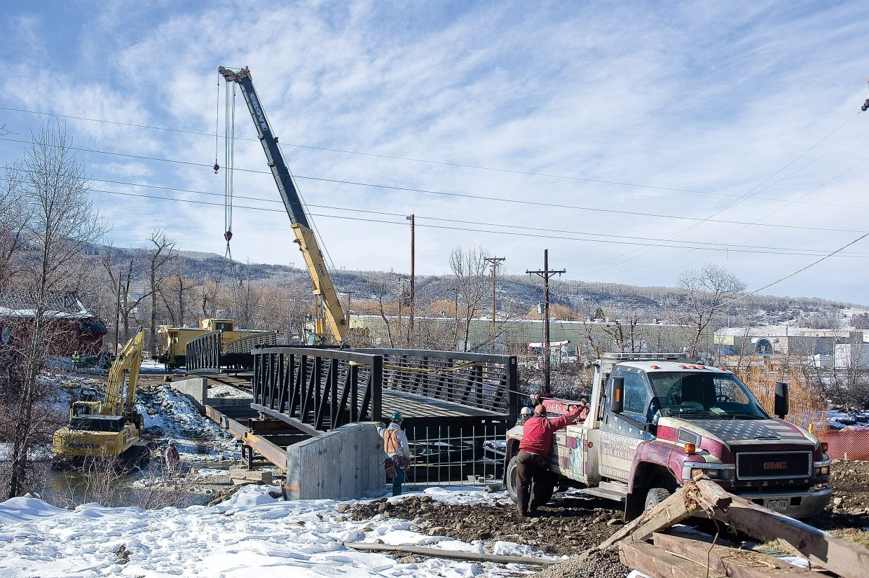 A tow truck is used Wednesday to pull a section of bridge across the Yampa River that will connect the Yampa River Core Trail in front of the Depot Art Center to West Lincoln Park.