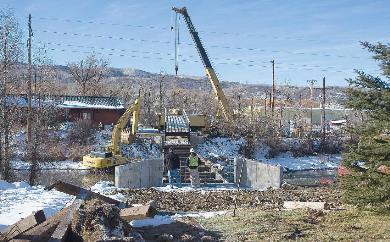 A crane positions a pedestrian footbridge Wednesday that will connect the Yampa River Core Trail in front of the Depot Art Center to West Lincoln Park when completed.