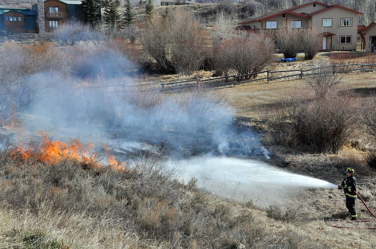 Steamboat Springs Fire Rescue firefighter Trevor Guire works to extinguish a wildfire Sunday afternoon in the Elk River Estates. The fire was caused by a homeowner who dumped smoldering fireplace ashes into a nearby creek.