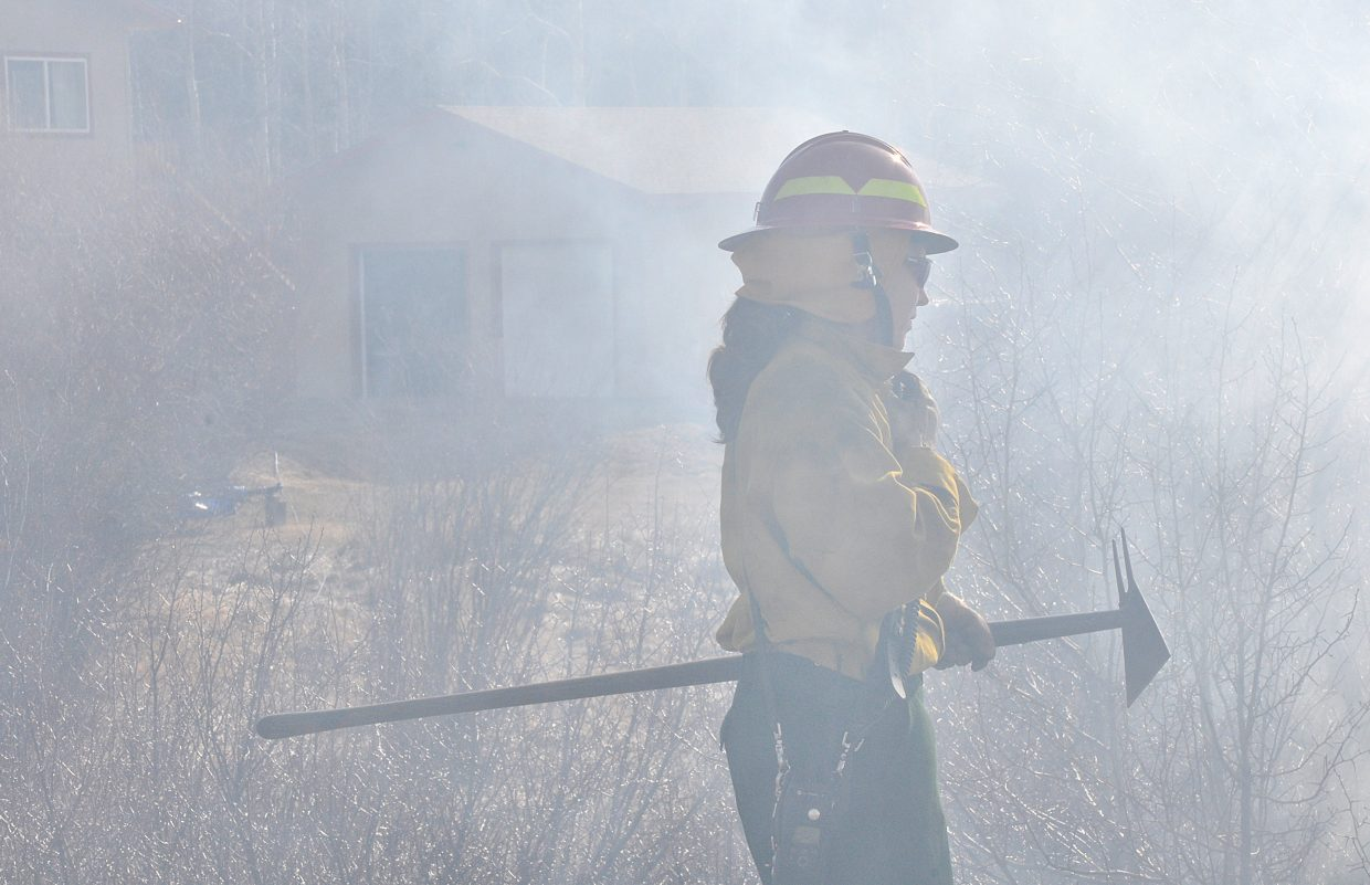 Steamboat Springs Fire Rescue firefighter Marnie Smith talks on a radio Sunday as she helps fight a wildfire in the Elk River Estates.