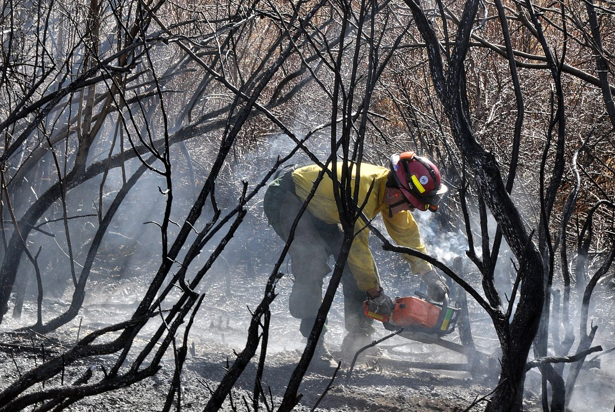 Steamboat Springs Fire Rescue firefighter Matt Mathisen uses a chainsaw Sunday to cut down smoldering brush at  the scene of a wildfire in Elk River Estates.