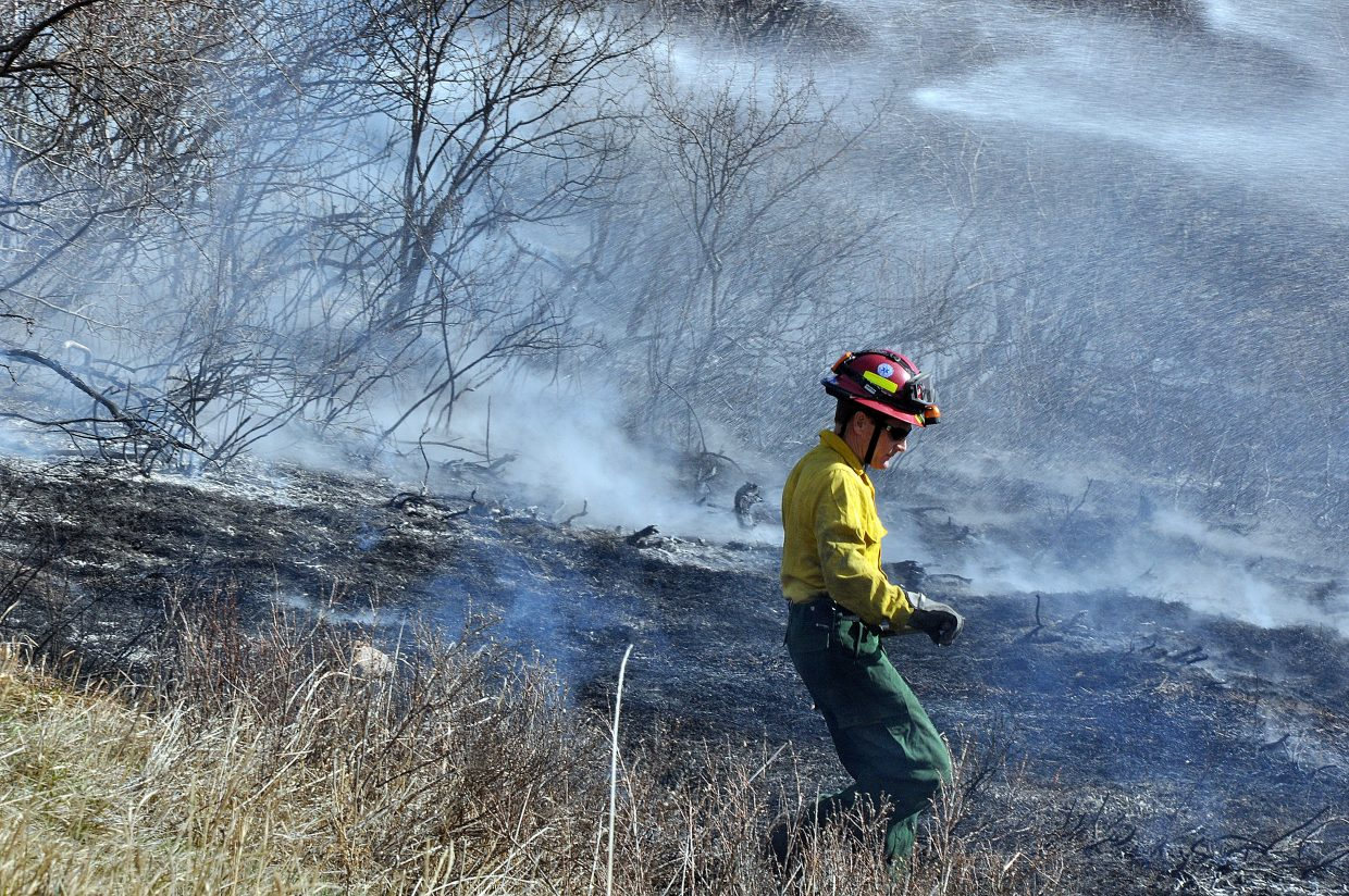 A Steamboat Springs Fire Rescue firefighter works Sunday to put out a small wildfire in the Elk River Estates.