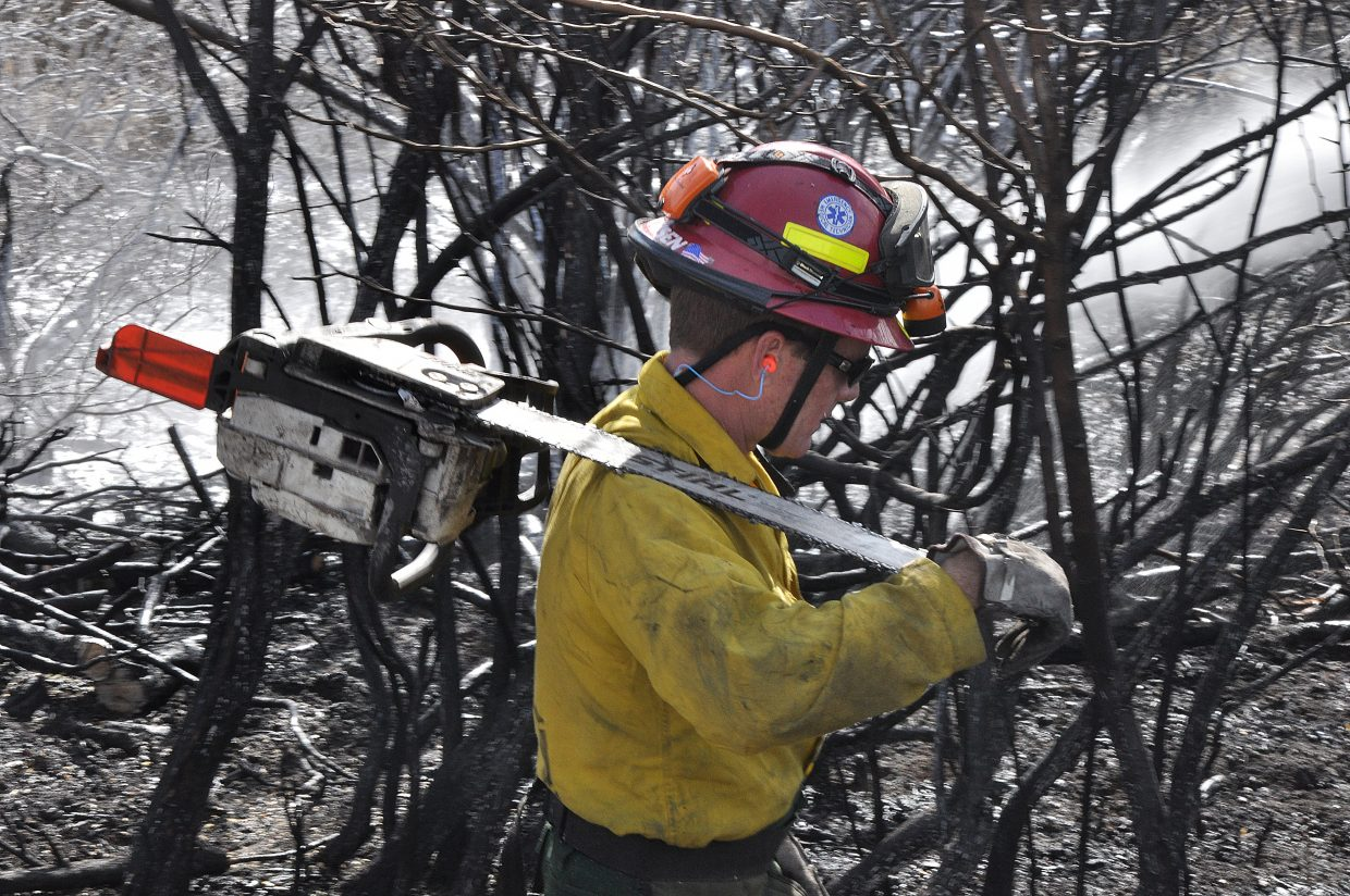 Steamboat Springs Fire Rescue firefighter Matt Mathisen finishes clearing brush Sunday at the scene of a wildfire at Elk River Estates.