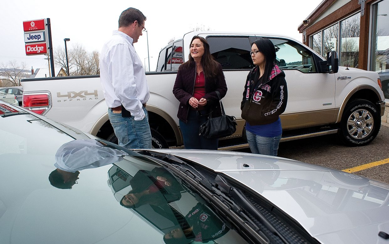 Bret Bissey, finance manager at Steamboat Motors, talks with customer Susan Gardner and her daughter Chelsea Juarez on Friday afternoon at the Steamboat Springs car dealership. Gardner recently moved to Steamboat Springs from California and was looking for a vehicle better suited to a Yampa Valley winter. Jeff Steinke, of Steamboat Motors, said his dealership's new-car sales are up this year.
