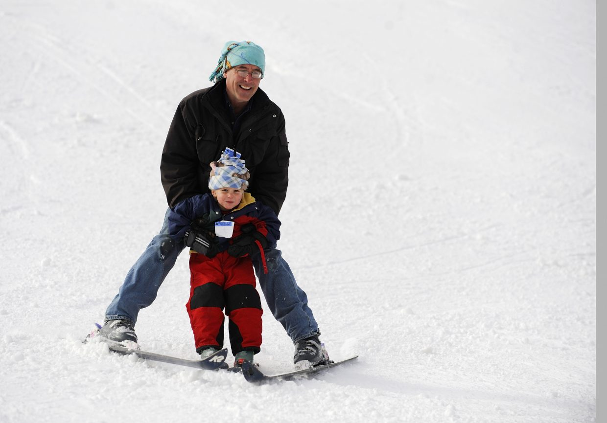 Tommy Leitner skis down Howelsen Hill with his 3-year-old son Stephen on Saturday during opening day at the historic downtown ski hill. Skiing was free during the community appreciation day.