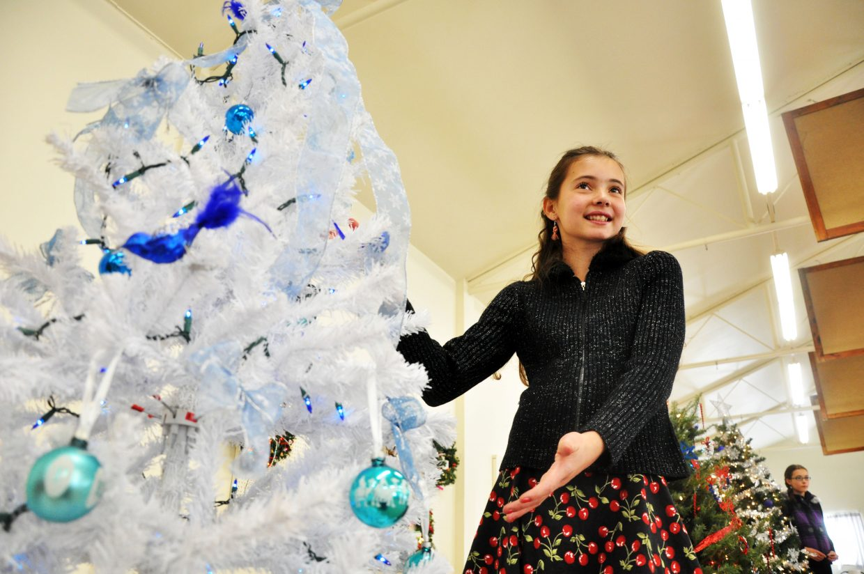 Michaela Villa models a Christmas tree up for auction Sunday at the Hayden Christmas Tree Festival. The auction raised more than $4,000 for 17 nonprofits in Routt and Moffat counties.