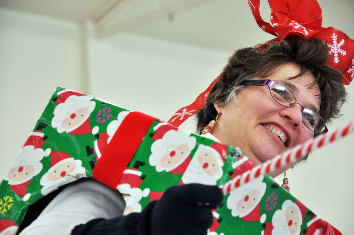 Laurie Hallenbeck takes bids Sunday at a Christmas tree auction in Hayden. Hallenbeck each year dresses up at the auction to get in the Christmas spirit, and this year she was a human-sized present.