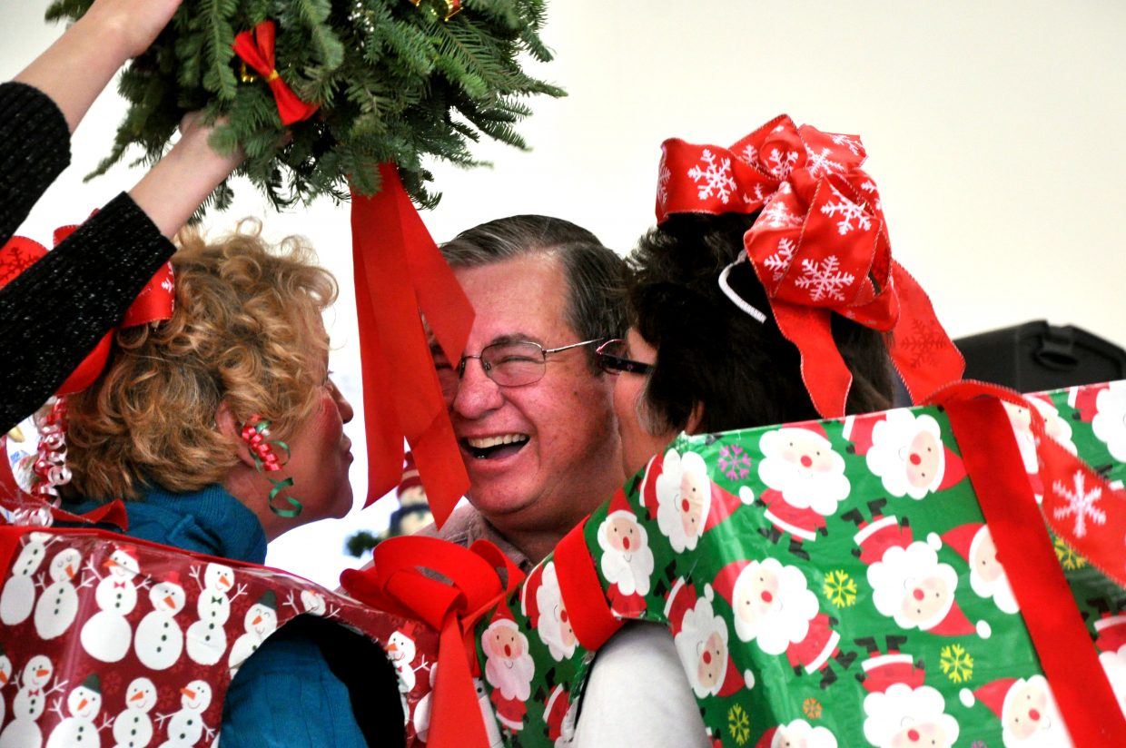 "Linda Archuleta, left, and Laurie Hallenbeck, right, move in to ""kiss"" auctioneer Kenny Kawcak under a mistletoe Sunday at the Hayden Christmas Tree Festival."