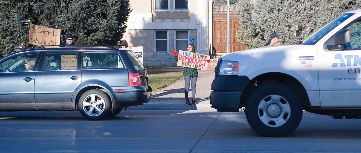 Ericka Rodriguez and a small group of people keep the Occupy movement alive Thursday in Steamboat Springs where they stood in front of the Routt County Courthouse and waved signs at passing motorists.