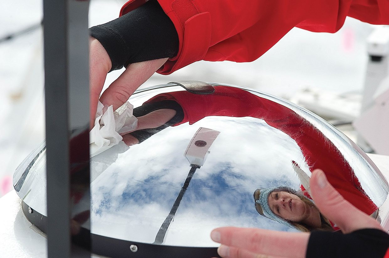 Scientist Nicki Hickmon cleans the mirror of a wide-angle camera that records the clouds from horizon-to-horizon at a research center near Yampa Valley Medical Center in Steamboat Springs. Hickmon is part of a five-month cloud study on Mount Werner where scientists are gathering information from sites at different elevations.
