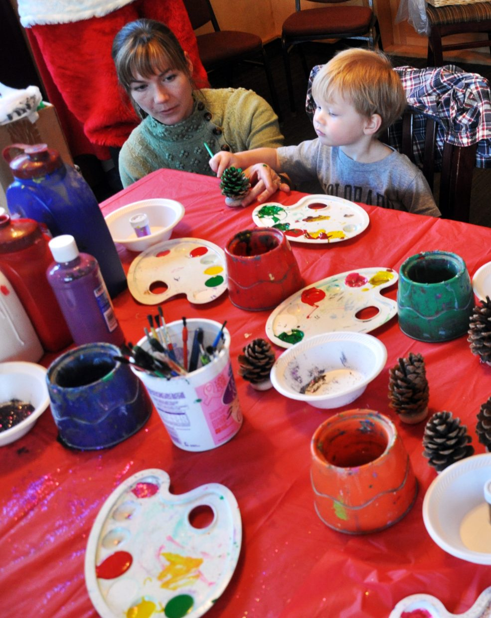 Michael Fairchild and his mother Stephanie paint pine cones Sunday at the Routt County United Way Holiday Wishes party.