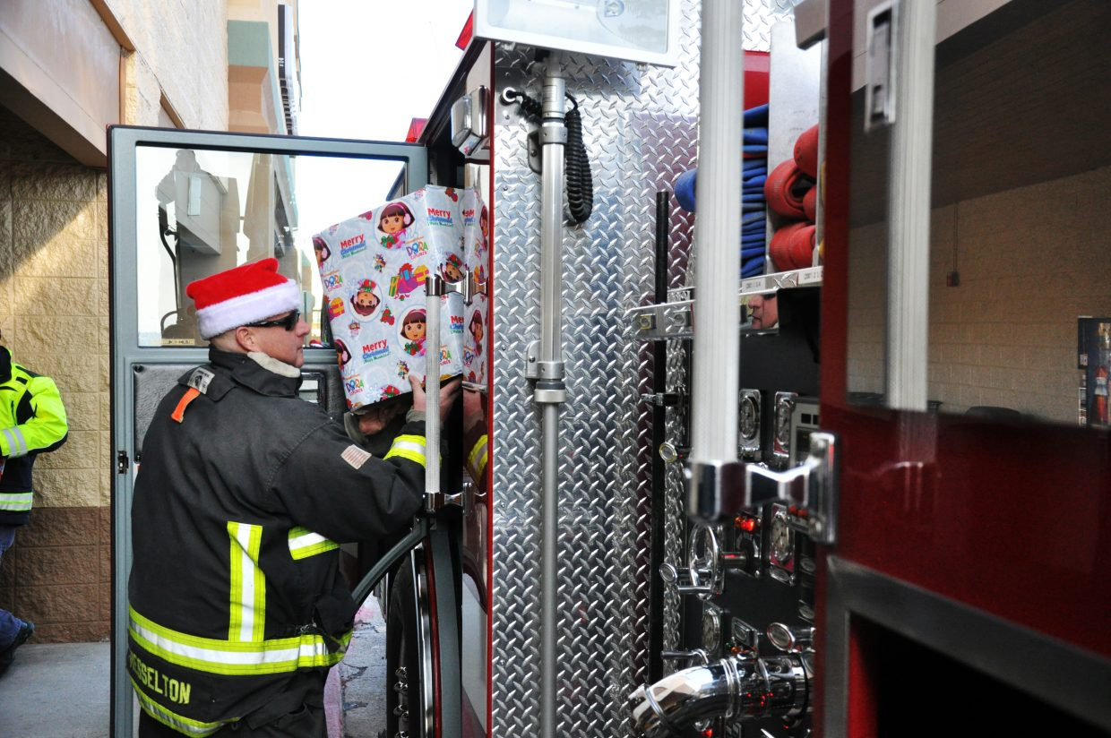 Steamboat Springs Fire Rescue firefighter Dave Hesselton loads a present into a fire engine Sunday outside of Walmart. The firefighters have collected more than 250 gifts for families during the Routt County United Way's Holiday Wishes campaign.