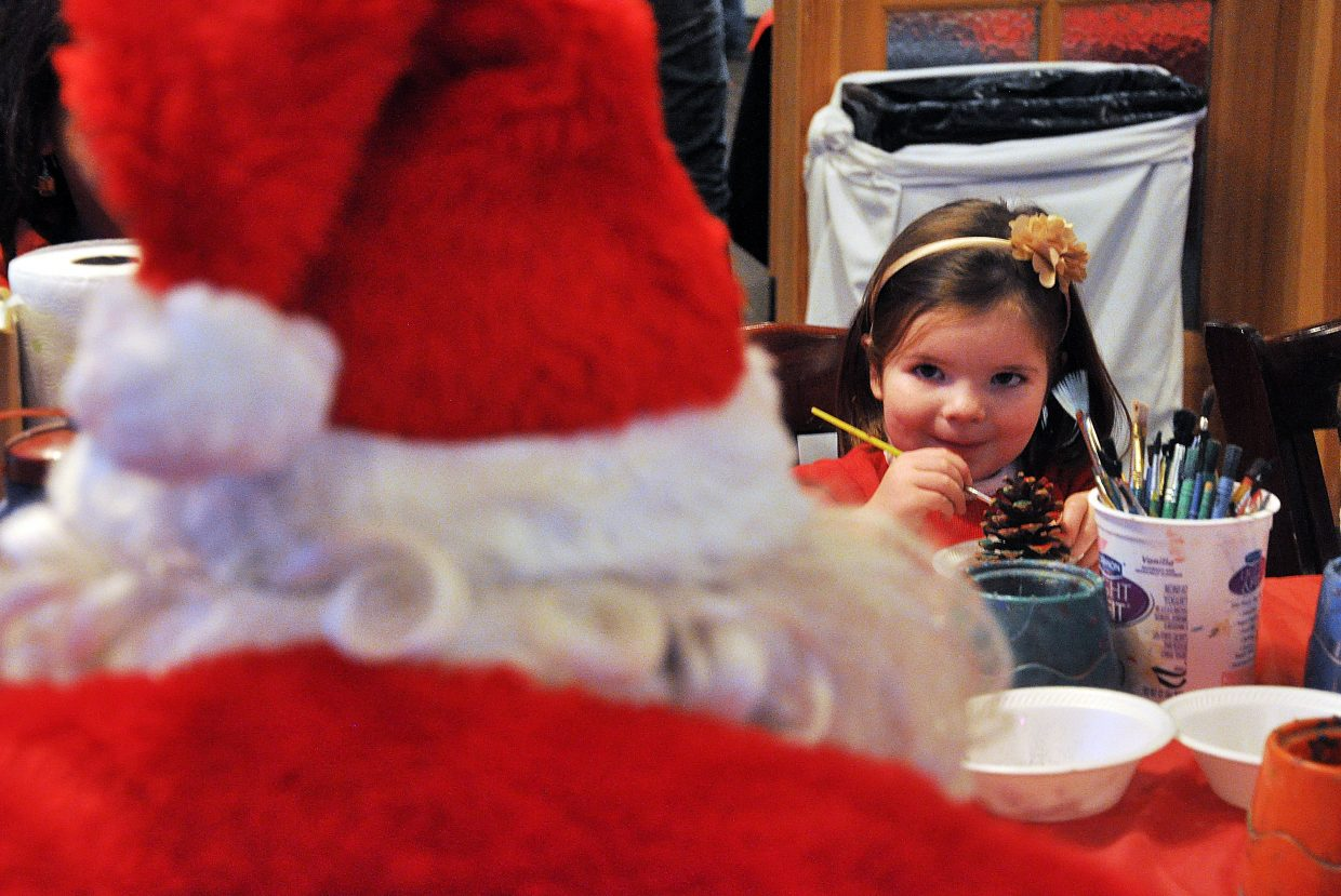 Marley Moore smiles at Santa while she paints a pine cone Sunday at the Routt County United Way Holiday Wishes party at Rex's American Grill & Bar. The party benefited 48 families who requested assistance in getting Christmas gifts.