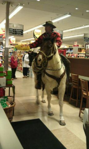 Michael Miller purchases a bag of tortilla chips on horseback Sunday at a Safeway store in Steamboat Springs. Miller was arrested later that evening after police said he was involved in a fight at the Old Town Pub.