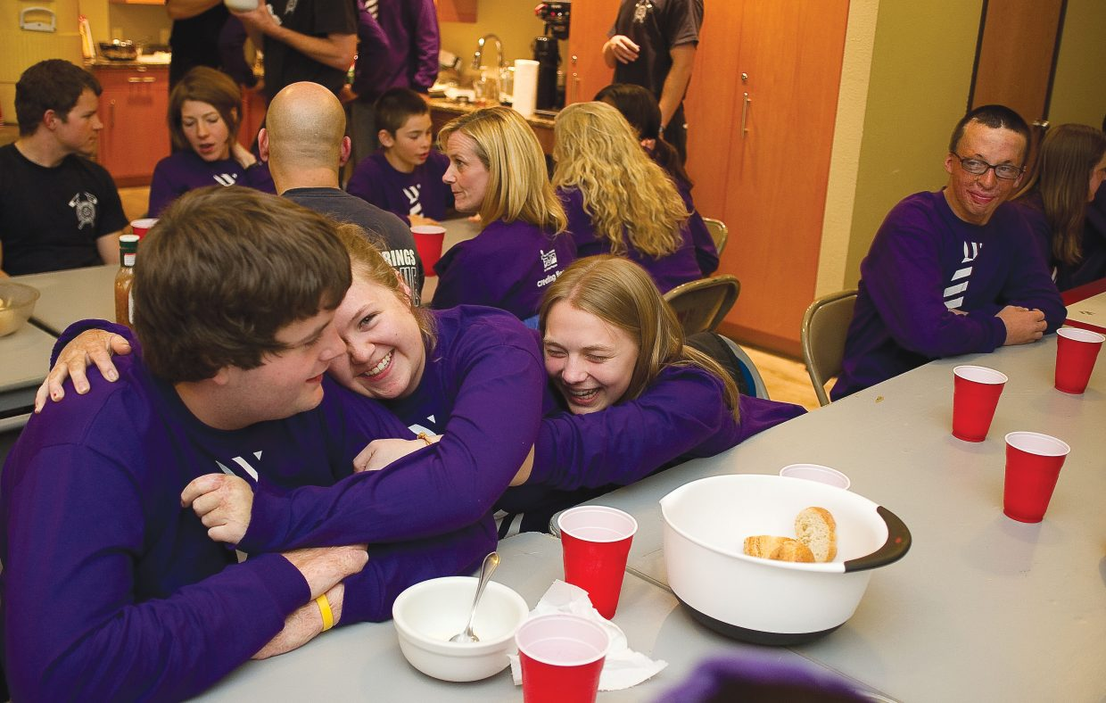Cody Baker gets a hug from fellow campers Sarah Reimann and Carley Boos during a dinner hosted by the members of Steamboat Springs Fire Rescue on Wednesday evening at the Mountain Station. The teens were in Steamboat Springs as part of the Children's Hospital Burn Camp Program. This week's camp brought teens from across the country to Steamboat Springs to share their experience and have fun on the slopes.