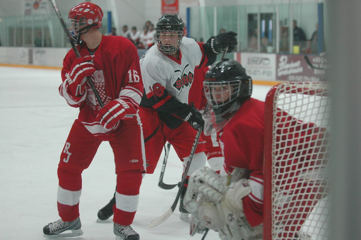 Steamboat Springs High School hockey player Ben Wharton, middle, looks for a rebound Saturday against Regis Jesuit. The Sailors ended up losing, 5-1.
