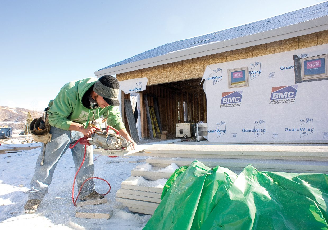 Evan Marks, of Skyline Construction Services, cuts a board while putting the siding on the new FBO building at the Steamboat Springs Airport on Thursday afternoon. Construction on the building, which will be used by private pilots flying in and out of Steamboat Springs, is ahead of schedule.