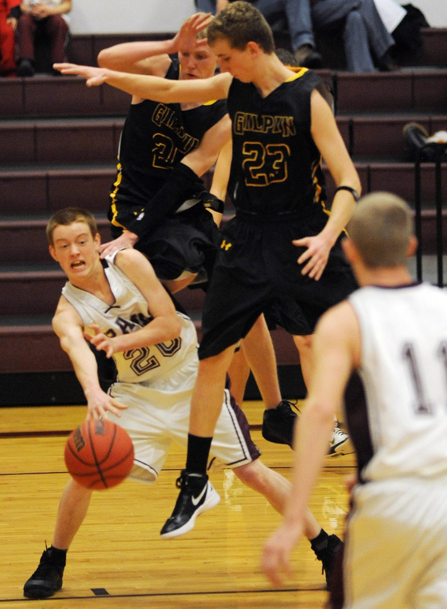 Soroco's Charley Fitzhugh slips the ball around a pair of Gilpin County defenders on Saturday.