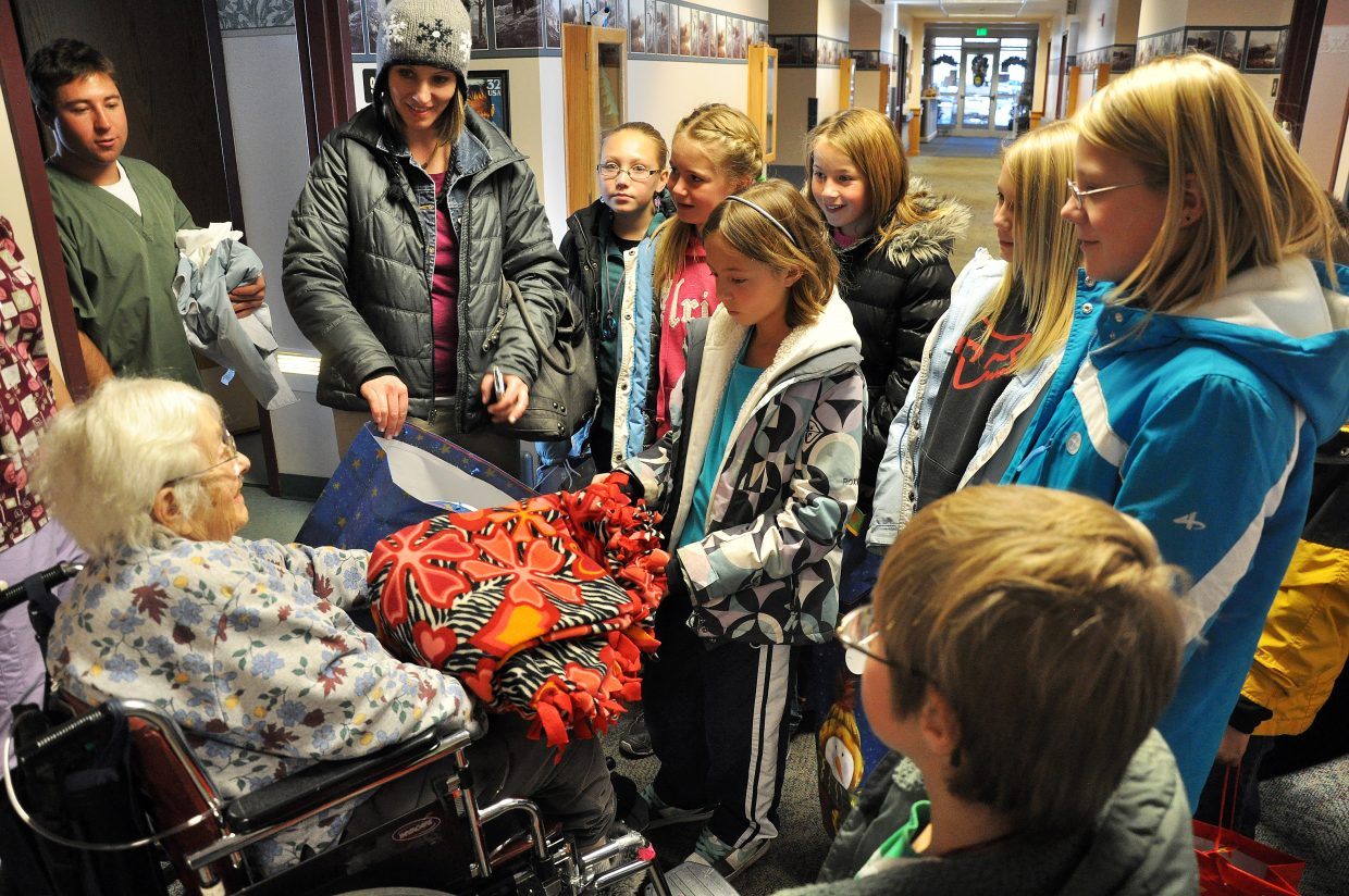 Hayden Elementary School Student Council students give Neva Brown a fleece blanket Thursday at the Doak Walker Care Center in Steamboat Springs. The students made the blankets as Christmas gifts and gave them to eight lucky residents at the care center.