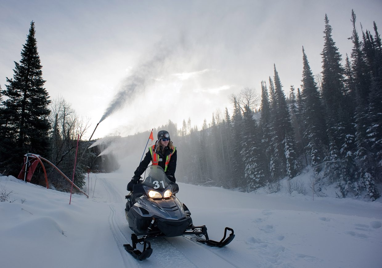 Snowmaking technician Pierce Delhaute jumps on his snowmobile after checking snowmaking equipment. Snowmakers must use snowmobiles to get around Steamboat Ski Area and often are required to ride them in extreme terrain and at all hours of the night.