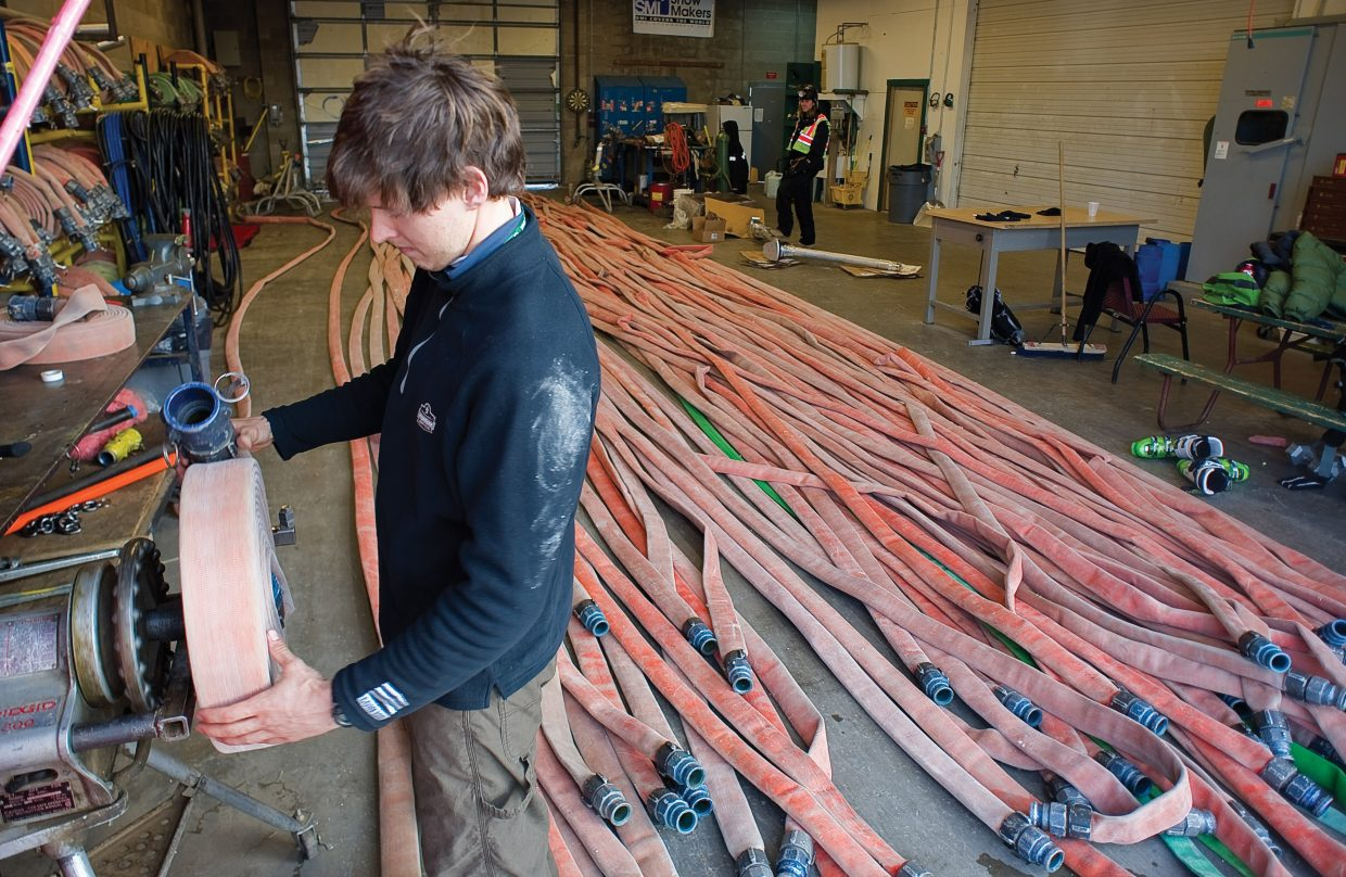Snowmakers Ben Rausch, front, and Michael Bryan roll up hoses used during snowmaking operations.