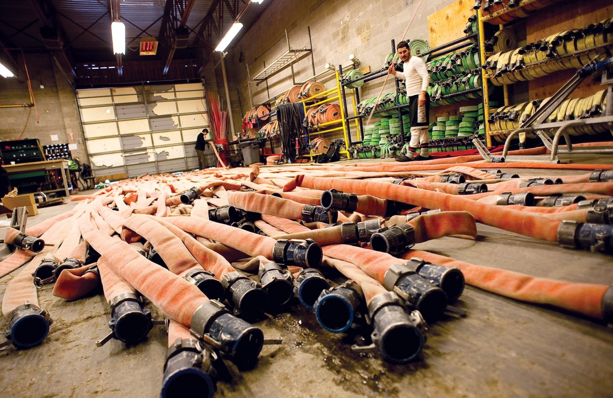 Snowmaker Michael Bryan, front, and Ben Rausch roll up hoses used during snowmaking operations.