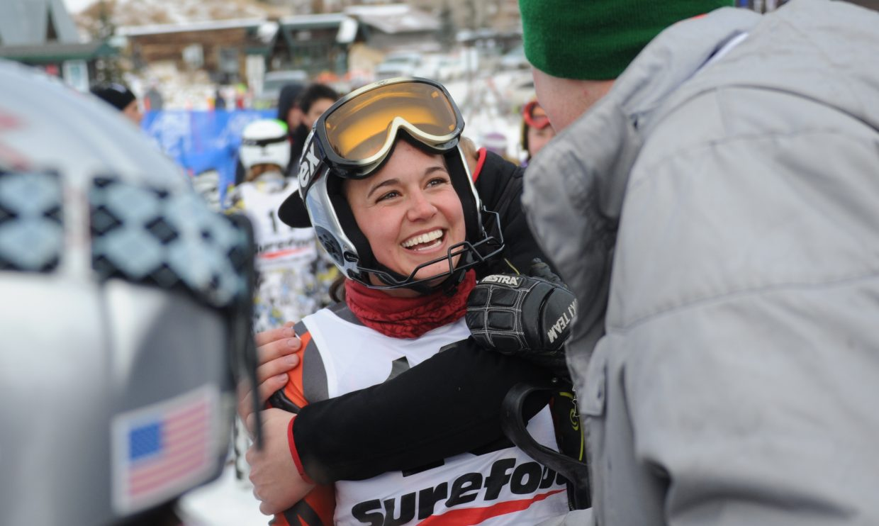 Mary Rachel Hostetter smiles wide while being crowded by friends after winning Thursday's slalom race at Howelsen Hill in Steamboat Springs.