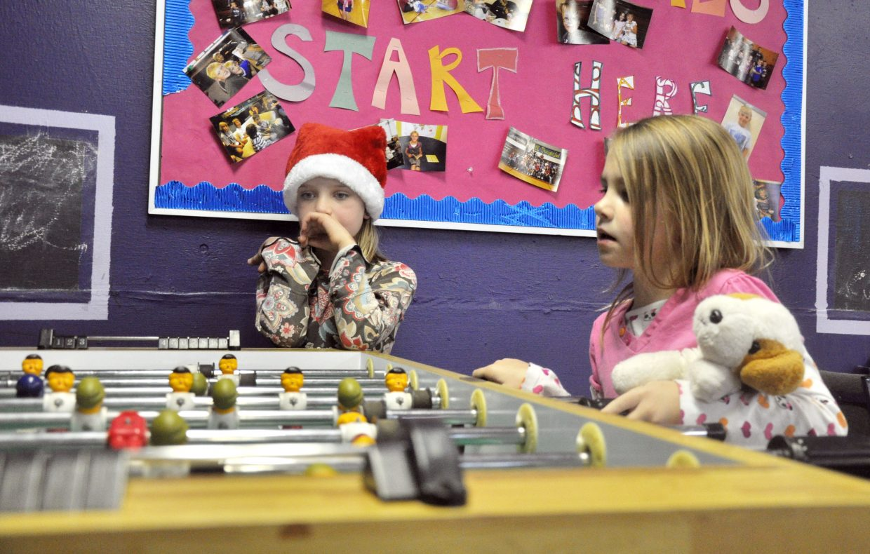 Tinsley Wilkinson, left, watches Izzy Mickelson play a game of foosball Wednesday at the Boys & Girls Club of Steamboat Springs. A holiday fundraising drive hosted by Yampa Valley Bank raised $9,161 for the club and allowed it to remain open on weekdays before and after Christmas.