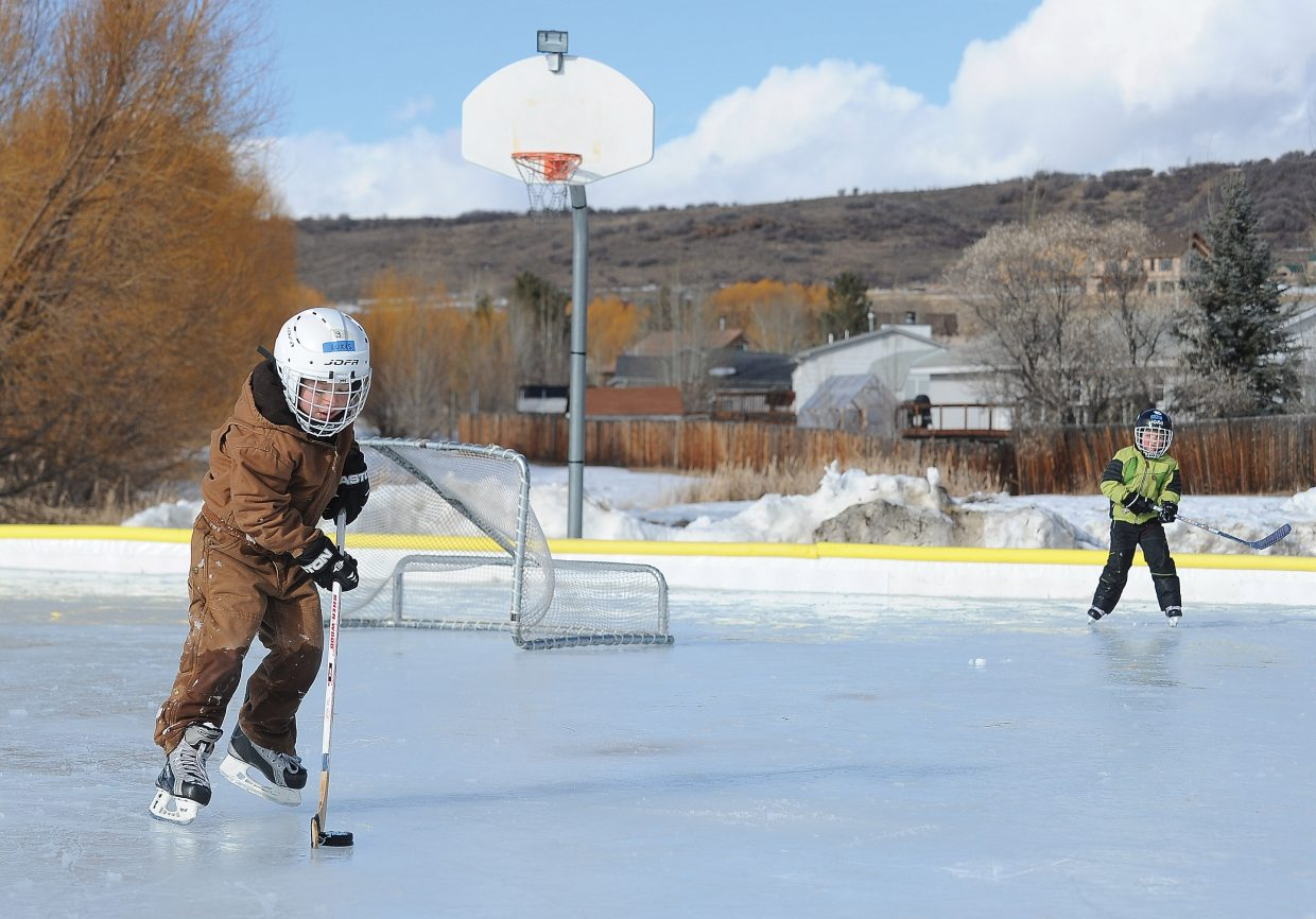 Lukas Znamenacek, front, and his brother Max play a game of hockey on the ice skating rink in Steamboat II on Thursday afternoon.