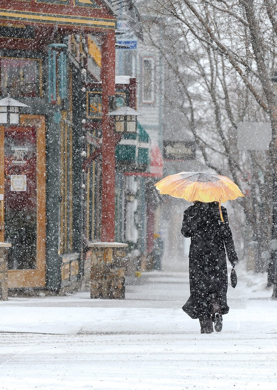 Kathy Dennis, who was visiting from Kentucky, walks through the snow falling Thursday in downtown Steamboat Springs. The snowstorm, which was heavy for a brief period of time, moved through the area quickly and was over early in the afternoon.
