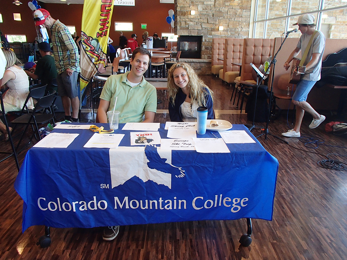 Colorado Mountain College student government advisor Chris Harnden, on left, and CMC student activities assistant Ashley Bernklau work at a booth at the CMC community fair on Aug. 29. Photo by: Todd Schuster. Submitted by: Debra Crawford.