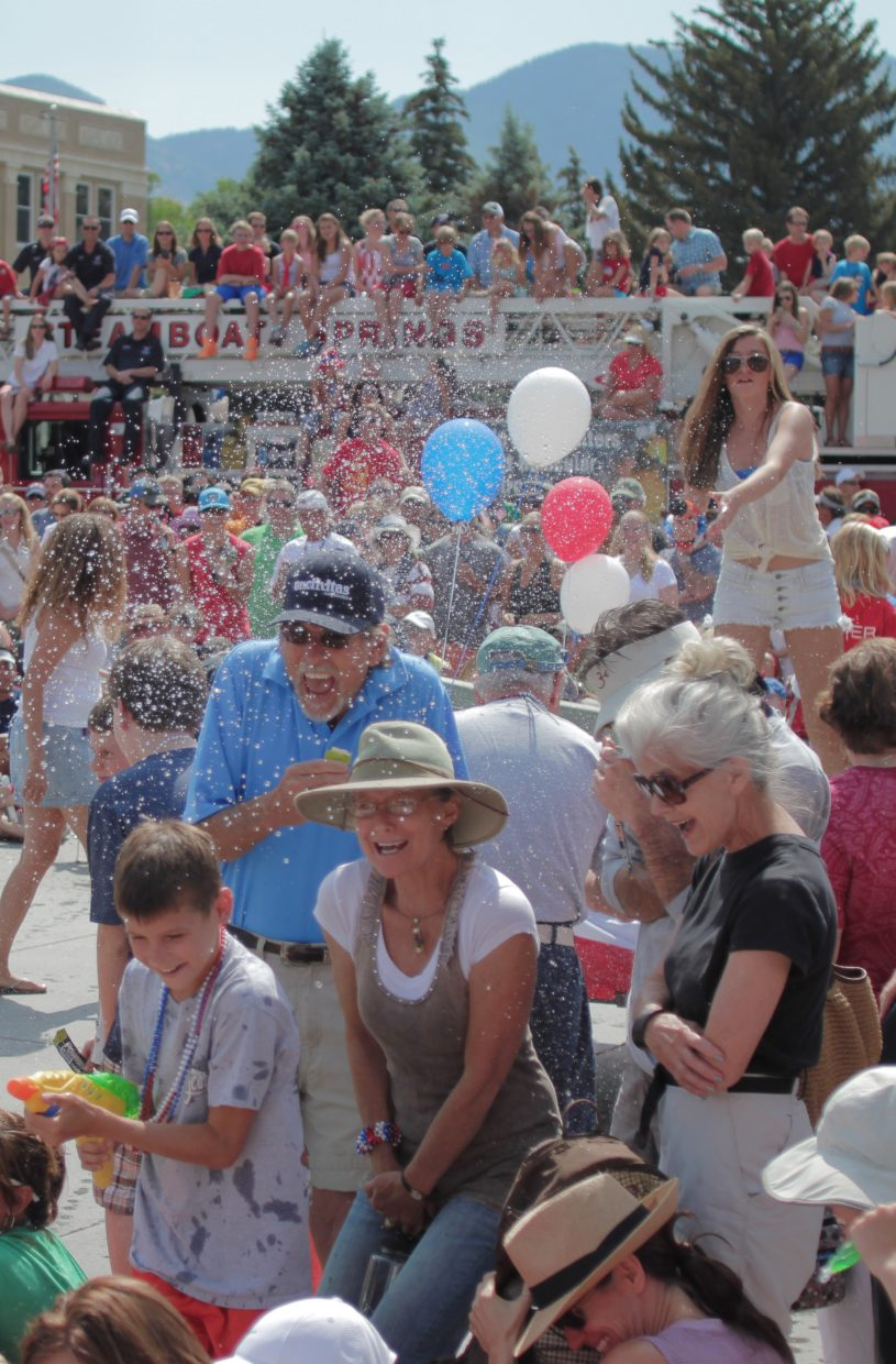 Parade-goers get blasted by a water gun from one of the floats. One boy, Jacob Rogers, lower left, came prepared to fight back. A fire truck hosts a number of young onlookers in the background. Submitted by: Ian Corry